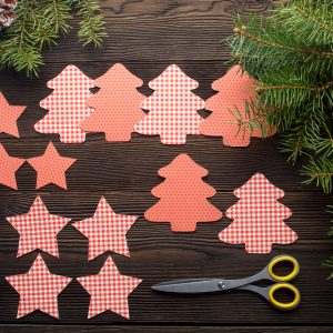 Christmas composition on wooden background with Christmas tree, pine cones, cardboard figures. Cardboard Christmas tree, stars and scissors. Cardboard figure on a wooden background